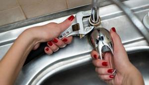 Manos de mujer tratando de cambiar grifo cocina